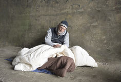Mature homeless man sitting in old blankets outdoors stock image