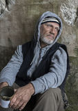 Mature homeless man sitting outdoors with a tin Royalty Free Stock Images