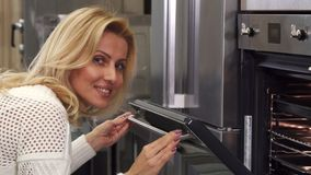 Mature housewife cooking at home smiling joyfully looking in the oven. Gorgeous mature blond haired woman looking in the oven while baking at home smiling to the royalty free stock photos