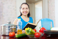Mature housewife dreams with book Royalty Free Stock Photos