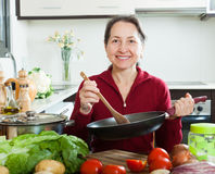 Mature housewife with frying-pan in home kitchen Stock Photography