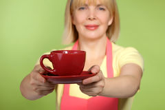 Mature housewife giving  cup of tea Stock Photography