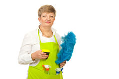 Mature housewife holding cleaning objects Stock Images