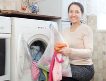 Mature housewife loading the washing machine Stock Photo