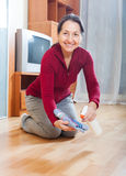 Mature housewife polishing parquet floor. With furniture polish royalty free stock photos