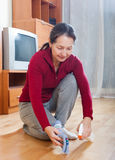 Mature housewife polishing parquet floor. With polish royalty free stock photo
