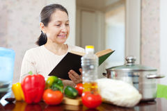 Mature housewife reads cookbook Royalty Free Stock Photo