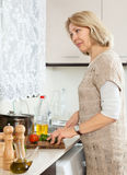 Mature housewife spliting veggy lunch Stock Photo
