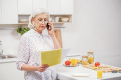 Mature housewife using phone for domestic chores Stock Photos