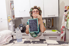 Mature housewife woman with curlers. Shows a board with hearts Royalty Free Stock Images
