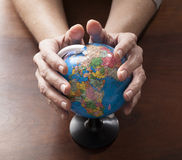 Mature human hands protecting the precious planet Stock Photography