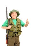 A mature hunter holding a rifle and giving a thumb up Royalty Free Stock Photography