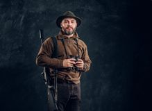 Mature hunter with rifle holding binoculars and looking at a camera. Studio photo against dark wall background royalty free stock photography