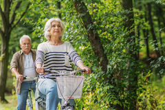 Mature husband and wife cycling in park stock images