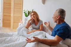Mature husband and wife having little quarrel in the bedroom royalty free stock images