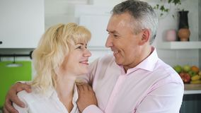 Mature husband and wife hugging in cozy kitchen. stock video footage