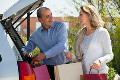 Mature husband and wife with shopping bags Stock Photography