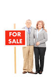 Mature husband and wife standing by for sale sign Royalty Free Stock Photography