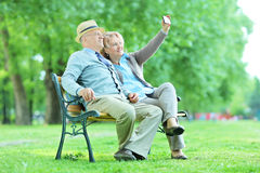 Mature husband and wife taking selfies in the park Stock Images