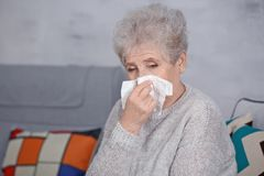 Mature ill woman with tissue at home Stock Image
