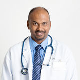 Mature Indian doctor smiling. Portrait of mature Indian male medical doctor in uniform smiling, standing on plain background with shadow royalty free stock photos