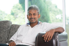 Mature Indian man. Portrait of mature Indian man sitting on sofa at home. Asian male relax on couch in house with interior Stock Photography