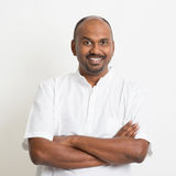 Mature Indian man smiling. Portrait of mature casual business Indian man arms crossed and smiling, standing on plain background with shadow stock image