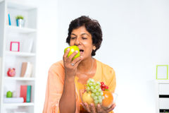 Mature Indian woman eating fruits Stock Image