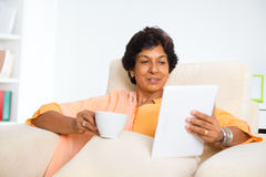Mature Indian woman using computer tablet. Mature 50s Indian woman drinking coffee / tea and using digital computer tablet at home Royalty Free Stock Photography