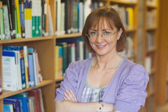 Mature intellectual woman posing in library Stock Photography