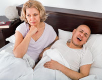 Mature irritated girl looking at snoring boyfriend. Sleeping tight Royalty Free Stock Photo