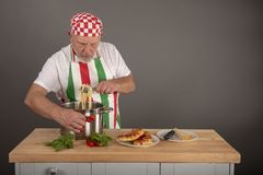 Mature Italian Chef plating up a pasta dish. In a kitchen setting royalty free stock photos