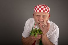 Mature Italian chef smelling basil leaves stock photography