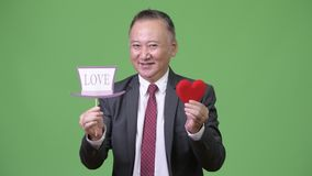 Mature Japanese businessman holding paper sign. Studio shot of mature Japanese businessman against chroma key with green background stock video