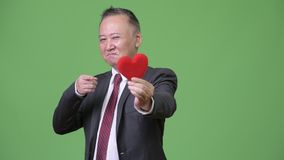 Mature Japanese businessman holding red heart ready for Valentine`s day. Studio shot of mature Japanese businessman against chroma key with green background stock video