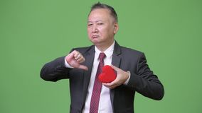 Mature Japanese businessman holding red heart ready for Valentine`s day. Studio shot of mature Japanese businessman against chroma key with green background stock video footage
