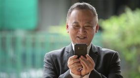 Mature Japanese businessman using phone in the streets outdoors