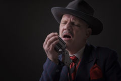Mature Jazz man singing into a microphone Stock Images