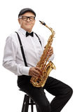 Mature jazz musician with a saxophone sitting on a chair Stock Photos