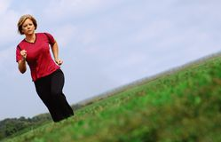 Mature Jogger. Mature woman jogging in a big summer field stock images