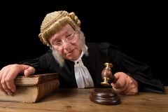 Judge decision. Mature judge with authentic court wig holding a gavel in court royalty free stock photography