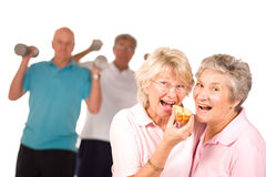 Mature ladies eating cake. Mature older ladies eating cake with partners working out in the background stock images