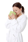 Mature lady in bathrobe drinking from mug Royalty Free Stock Photos