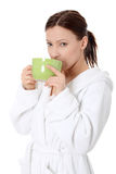 Mature lady in bathrobe drinking from mug Stock Photo