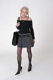 Mature Lady with big bag. Mature Lady in mini-skirt with a big shoulder bag Royalty Free Stock Photo