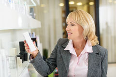 Mature lady buying cosmetics in store Royalty Free Stock Images