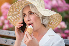 Mature lady with cell phone. Woman eats ice cream. Now listen carefully. Latest news from home royalty free stock photography