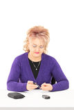 Mature lady checking her blood sugar level Royalty Free Stock Photography