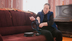 Mature lady checks her health state with manual manometer - measures pressure - pensioner alone at home Royalty Free Stock Photos