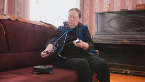 Mature lady checks her health state with manual manometer - measures pressure - pensioner alone at home Royalty Free Stock Images